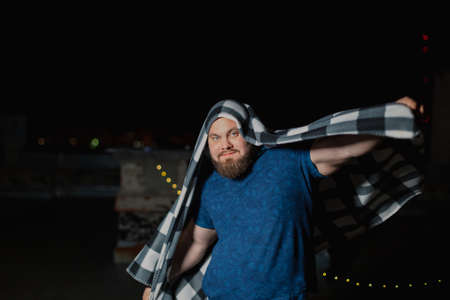 Big bearded man covered with a blanket.