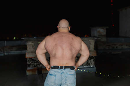 Big bearded bodybuilder on the rooftop in the evening. 免版税图像