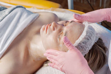 Professional beautician makes a facial massage to a woman.