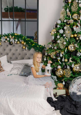 Beautiful little girl sitting by a Christmas tree with a lantern in her hands.