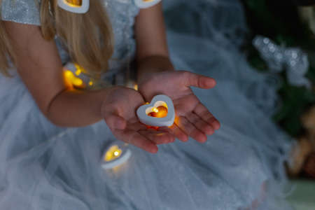 Beautiful little girl holding Christmas candles in her hands while sitting on the bed. Imagens
