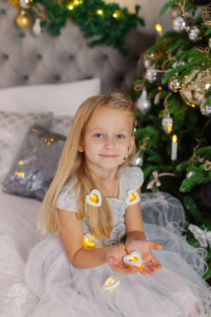 Beautiful little girl holding Christmas candles in her hands while sitting on the bed.