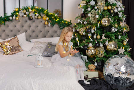 Beautiful little girl holding Christmas candles in her hands while sitting on the bed. Stok Fotoğraf