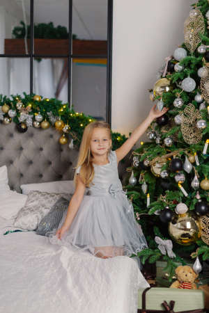 Beautiful little girl takes off a Christmas toy from the tree.