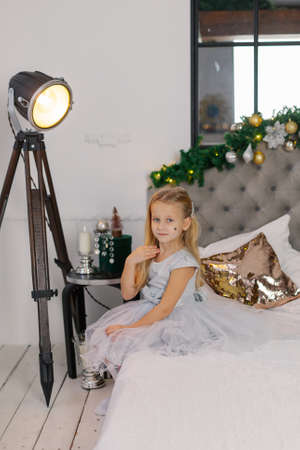 Beautiful little girl sitting on the New Years bed.