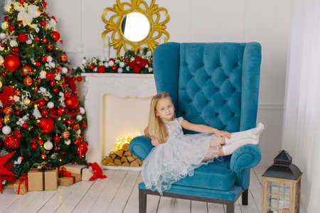 Beautiful little girl sitting on a chair by the tree.