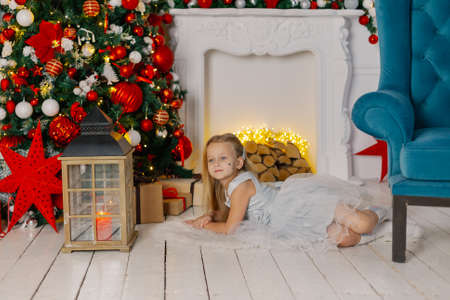 Beautiful little girl lies on the floor by the tree and the fireplace in the background. Stok Fotoğraf