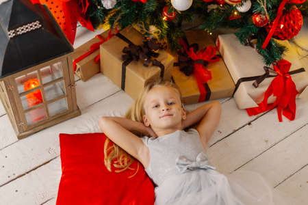 Beautiful little girl lies on the floor by the tree. Stok Fotoğraf