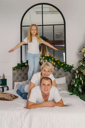 Beautiful young happy family on the new years bed. Stok Fotoğraf