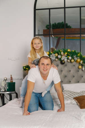 Young happy dad and little daughter on the new years bed.