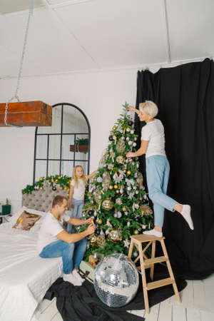 Beautiful young happy family decorate the christmas tree. Stok Fotoğraf