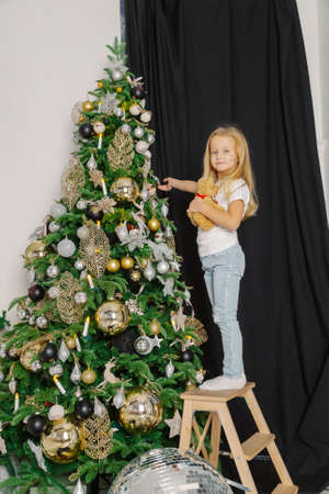 Beautiful little girl decorates a christmas tree while standing on the stairs. Stok Fotoğraf