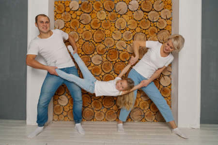 Beautiful happy young family rejoice at the wooden wall.