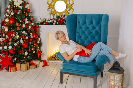 Beautiful young cheerful woman on an armchair near a Christmas tree.