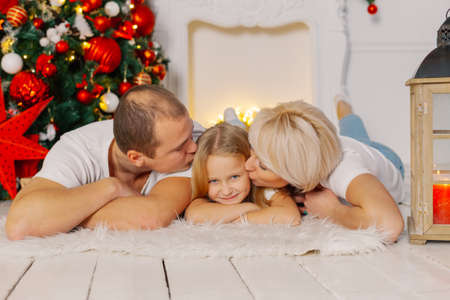 Beautiful young happy family lies on the floor by the Christmas tree.