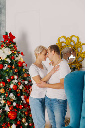 Young beautiful couple by the Christmas tree. Stok Fotoğraf