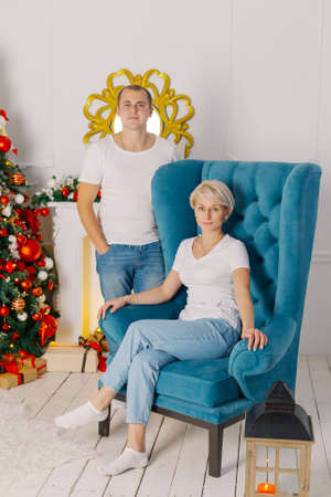 Young beautiful couple at the christmas tree on the armchair.