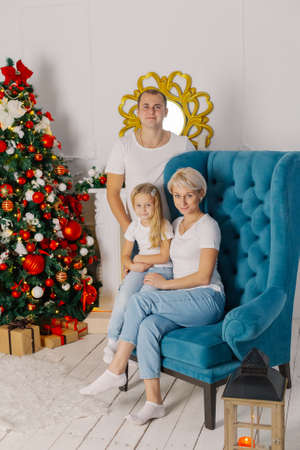 Beautiful young happy and cheerful family on an armchair near the New Year tree.