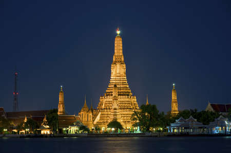 Wat Arun, the famous buddhist temple of the dawn, at night next to the Chao Phraya river, Bangkok, Thailand. photo