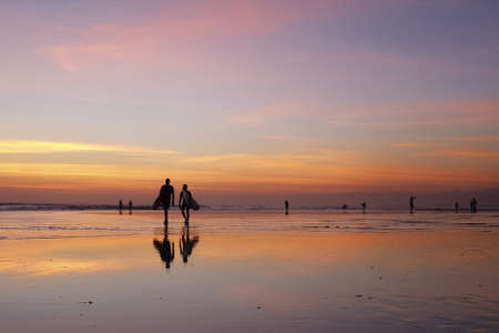returning: Kuta, Bali, Indonesia - August 10, 2013  Surfers returning to the beach after sunset