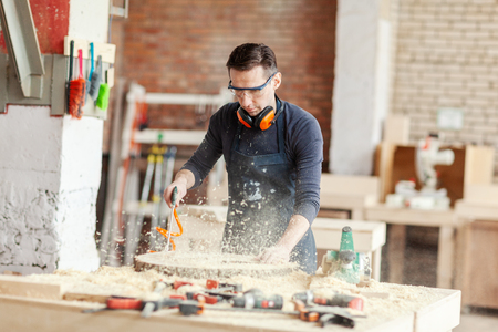 Young woodworker in safety goggles blowing sawdust off from wood slice at workbench on blurred background