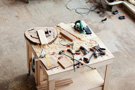 Von oben Blick auf Holzbearbeitungswerkzeuge, Holzscheiben, Bretter und Sägemehl auf der Werkbank in der Tischlerei