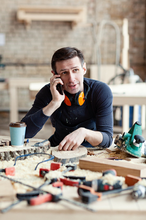 Young woodworker talking on mobile phone at workbench surrounded by tools and wood slices Imagens