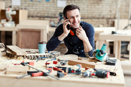 Portrait of young smiling carpenter talking on mobile phone at workbench surrounded by tools, wood slices and paper coffee cup