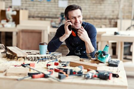 Retrato de joven carpintero sonriente hablando por teléfono móvil en el banco de trabajo rodeado de herramientas, rodajas de madera y taza de café de papel
