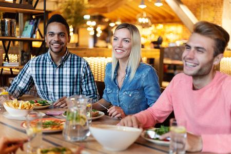 Grupo de jóvenes amigos multiétnicos cenando en el café, hablando y riendo