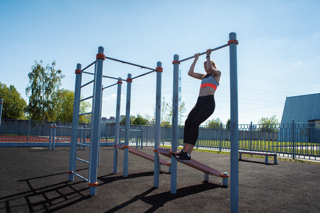 Slim teen girl in sportswear doing chin ups exercises at outdoor workout station