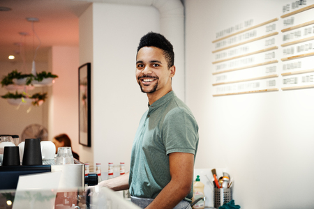 Side view of happy ethnic bartender looking at camera and standing at counter in coffee shop