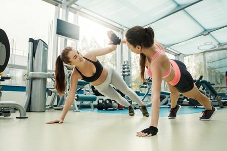 Jeunes amis minces attrayants en vêtements de sport faisant des exercices de presse et donnant cinq dans une salle de sport moderne Banque d'images