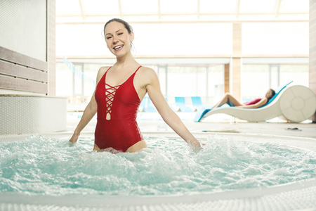 Young attractive positive woman having fun and resting in hot water of tub with hydromassage in spa