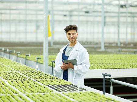 Erwachsener bärtiger Mann im weißen Mantel, der Tablette hält und in die Kamera lächelt, die im grünen modernen Komplex der Landwirtschaft steht