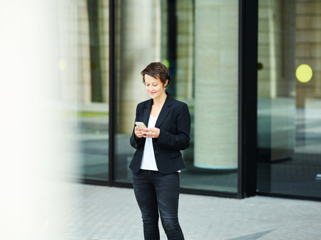 Stylish adult woman in black suit standing outside on street and surfing smartphone with smile Stockfoto