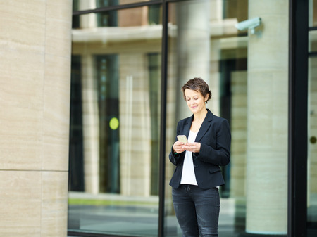 Trendy middle-aged woman in black jacket browsing smartphone with smile on background of contemporary building exterior