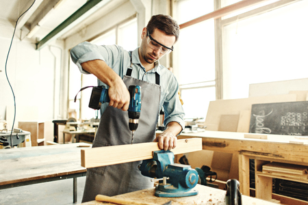 Concentrated young carpenter drilling hole in piece of timber using portable electric drill in his woodworking workshop