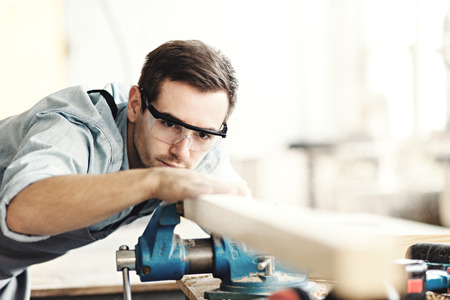 Skilled carpenter in protective eyewear touching piece of wood after sanding it on workbench Stock Photo