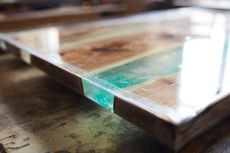 Closeup shot of modern wooden table top with epoxy resin element covered with lacquer Stock Photo