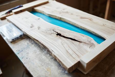 Piano del tavolo in legno preparato per resina epossidica sulla scrivania in falegnameria
