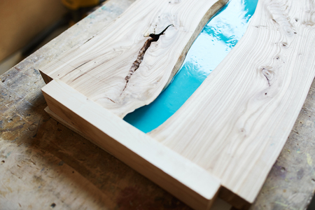 From above of composed wooden planks of table with place for epoxy resin on desk in joinery