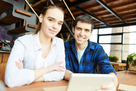Millennial man and woman sitting at desk with tablet computer and smiling at camera confidently