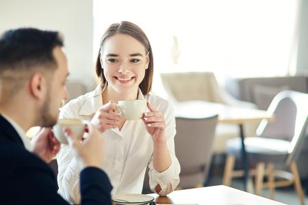 Giovani uomini d'affari, uomo e donna, che parlano amichevolmente al bar. Uomo d'affari e donna d'affari che si godono la riunione del caffè in rete. Concentrati sulla giovane donna sorridente che tiene una tazza di caffè Archivio Fotografico