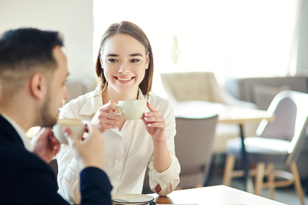Young business people, man and woman, having friendly talk in cafe. Businessman and businesswoman enjoying networking coffee meeting. Focus on smiling young woman holding cup of coffee Stockfoto