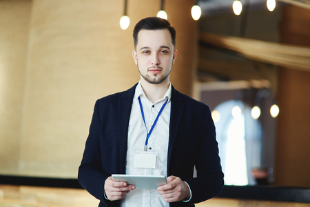 Waist-up portrait of business conference attendee looking at camera with tablet computer in his hands, empty badge around his neck Фото со стока