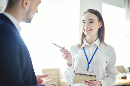 Smiling young businesswoman having friendly talk with male colleague while networking at business conference