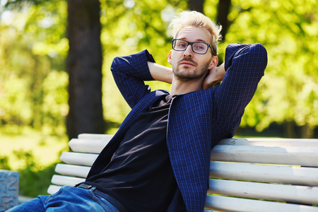 Blond male in glasses and dark jacket sitting on white park bench leaning on back with hands behind head and looking away on blurred background on sunny day