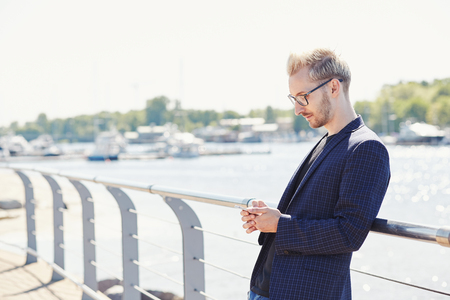 Relaxed young handsome man in glasses and dark jacket standing with mobile phone and leaning back on shiny metal handrail on sunny day with water and boats on blurred background