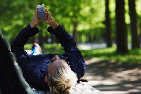 Blond male in glasses and checkered jacket lying on back on white park bench and looking at mobile phone in stretched out arms on sunny summer day on blurred background Imagens